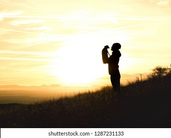 silhouette of woman with chihuahua at sunset