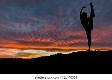 Silhouette of woman dancing and exercising on mountain top with sunset sky in the background.