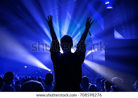 Silhouette of a Woman Dancing Whilst Sat On Someones Shoulders at a Pop Concert