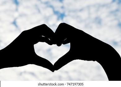 silhouette woman do heart-shaped hand