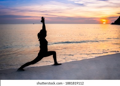 Silhouette of woman does warrior 1 yoga pose on the beach in the evening with sunset view and cloudy sky beside the calming sea during the holiday weekend. Capture at Phuket, Thailand.