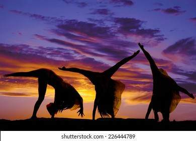 A silhouette of a woman doing a cartwheel.
