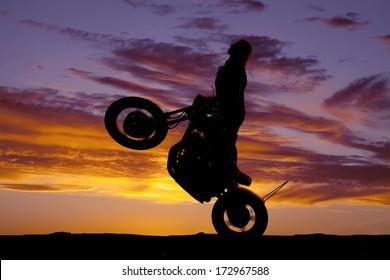 A silhouette of a woman doing a wheelie.