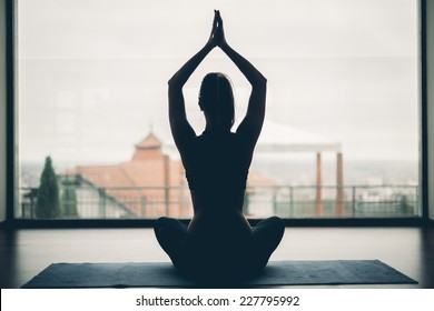 A silhouette of a woman doing yoga