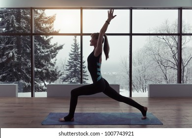 A silhouette of a woman doing yoga on background of windows with beautiful winter landscape with trees in the snow and sunlight, young yogi girl in warrior's position