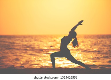 Silhouette of woman doing yoga outdoors ,female practicing fitness exercise on the beach at sunset , lifestyle relaxation wellness ,Healthy  Concept