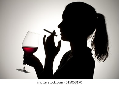 Silhouette of a woman drinking red wine and smoking.  Alcohol and substance abuse concept