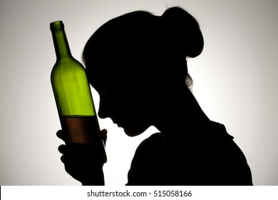 Silhouette of a woman drinking wine from the bottle and smoking.  Alcohol and substance abuse concept