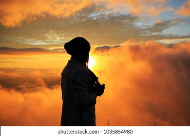 Silhouette of woman during sunrise with natural golden sunlight on Thailand mountain.