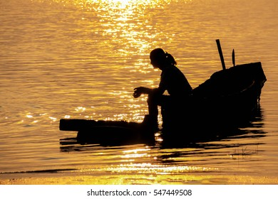 Silhouette of  woman enjoying summer sunset  over the sea sitting on the boat at the beach.