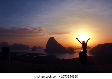 Silhouette woman of free cheering woman hiker open arms at mountain top cliff edge in morning with vintage light.