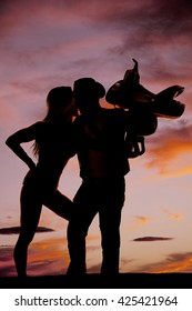 A silhouette of a woman giving her cowboy a kiss.