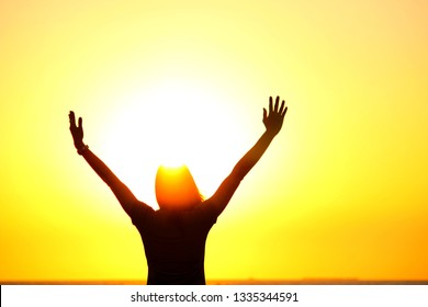 The silhouette of a woman with a golden sky during the sunset