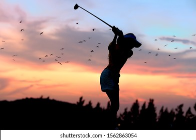 silhouette of woman golfer in an action of completed down swing hit a golf ball away to fairway in the golf course at sunset