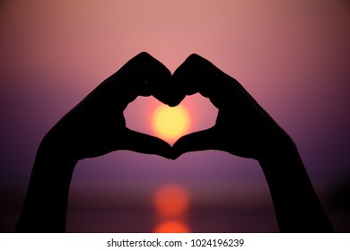 Silhouette the woman hands to be heart shape on sunset background. Happy, Love, Valentine's day idea, sign, symbol, concept.