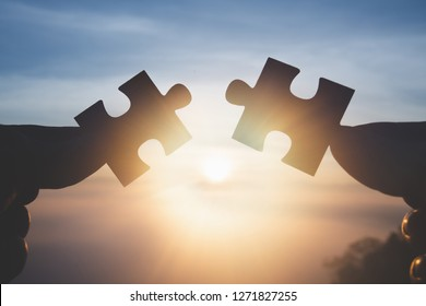 Silhouette Woman hands connecting couple jigsaw puzzle piece against sunrise, Business solutions, target, success, goals and strategy concepts