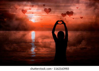 Silhouette of woman hands in heart shape with artistic dark red sunset.