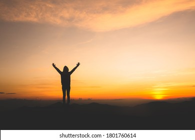 Silhouette of a woman with hands raised in the sunset concept for religion, worship, prayer and praise.