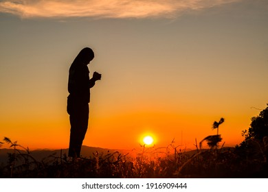 Silhouette of a woman with hands raised in the sunset concept for religion, worship, prayer and praise