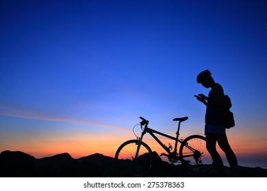 Silhouette of woman and her bike on rock mountain with sunrise twilight background.