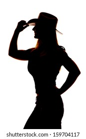 A silhouette of a woman in her cowgirl hat holding on to the brim of the hat.