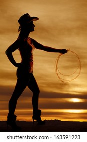 A silhouette of a woman in her cowgirl hat and she is holding on to her rope