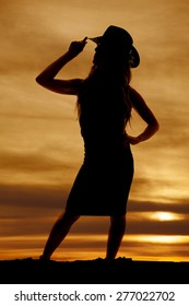 A silhouette of a woman in her dress with her western hat.