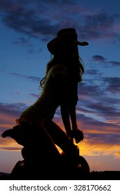 A silhouette of a woman in her western hat, kneeling on her saddle in the outdoors