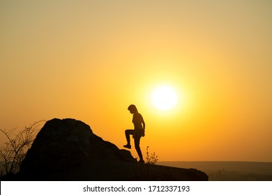 Silhouette of a woman hiker climbing up a big stone at sunset in mountains. Female tourist on high rock in evening nature. Tourism, traveling and healthy lifestyle concept.
