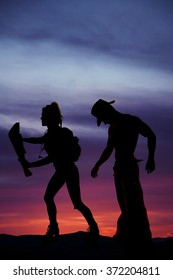 a silhouette of a woman hiker with a map, with a man standing close behind her.