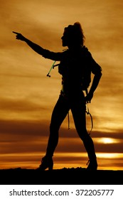A silhouette of a woman hiker pointing in the direction to go.
