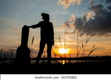 Silhouette with a woman holding acoustic guitar case on sunset