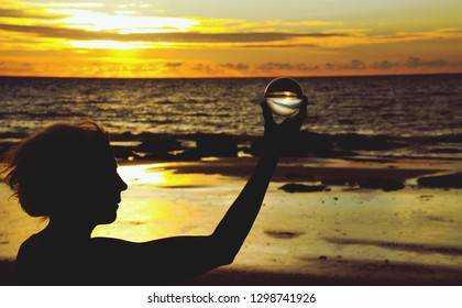 Silhouette of woman holding a crystal ball into beautiful sunset on Ko Lanta, Thailand