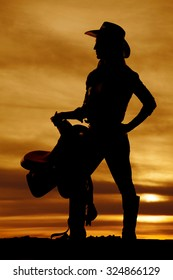 a silhouette of a woman holding on to her saddle, with her cowgirl hat on.