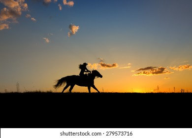Silhouette or woman and horse running across horizon as the sun goes down.