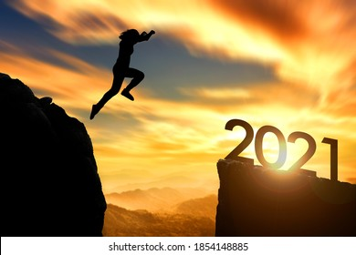 Silhouette woman jumping to 2021 cliff on sunrise time.