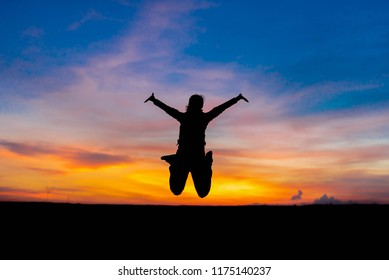 Silhouette woman jumping happily relieved.