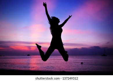 Silhouette of a Woman Jumping on a Beach
