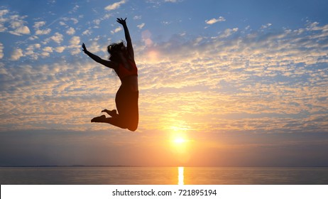 Silhouette of woman jumping on the beach, twilight, concept black body, copy space