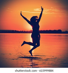 Silhouette of a woman jumping in the water at sunset