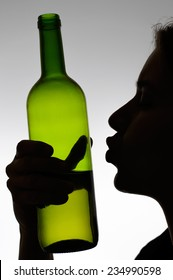 Silhouette of a woman kissing a wine bottle