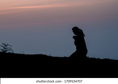Silhouette of woman kneeling on mountain and praying over beautiful sunrise background