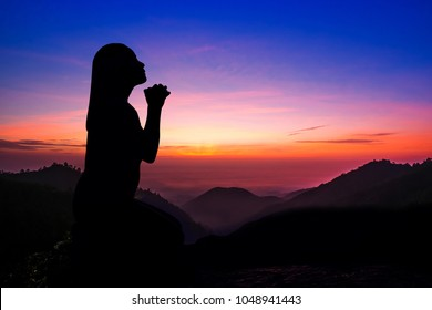Silhouette of woman kneeling and praying over beautiful sunrise