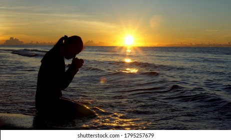 Silhouette of woman kneeling and praying over beautiful sunrise at sea background