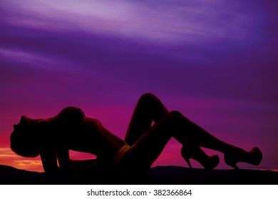 A silhouette of a woman leaning back with her chest up.