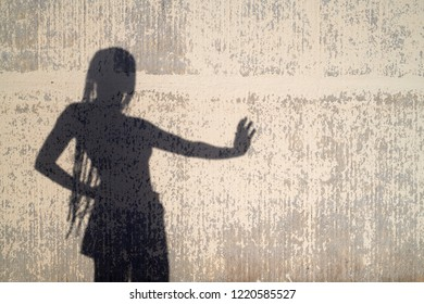 Silhouette of woman with long afro braids showing stop gesture. Silhouette on the wall in sunlight.