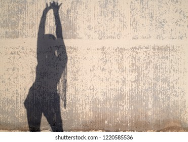Silhouette of a woman with long afro braids stretching her arms up in the air over worn-out sunlit wall. Copyspace.