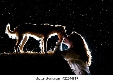 Silhouette of a woman with long hair kissing her little dog at sunset. Manifestation of love for your dog