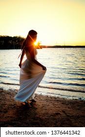 Silhouette of woman in long white dress along a lake shore