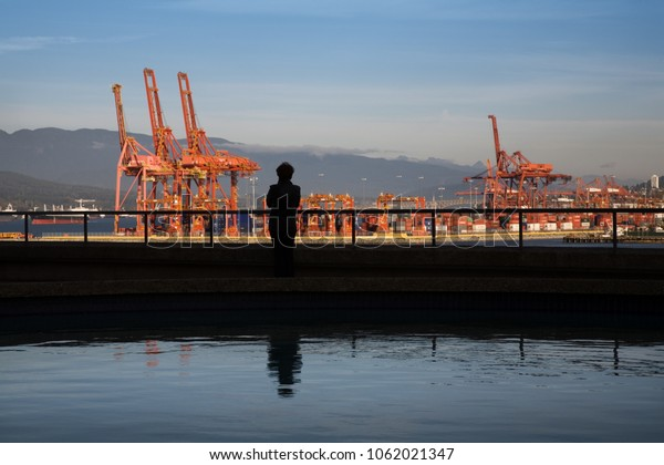 Silhouette of woman looking over cranes and brightly coloured containers of Vancouver Harbour.